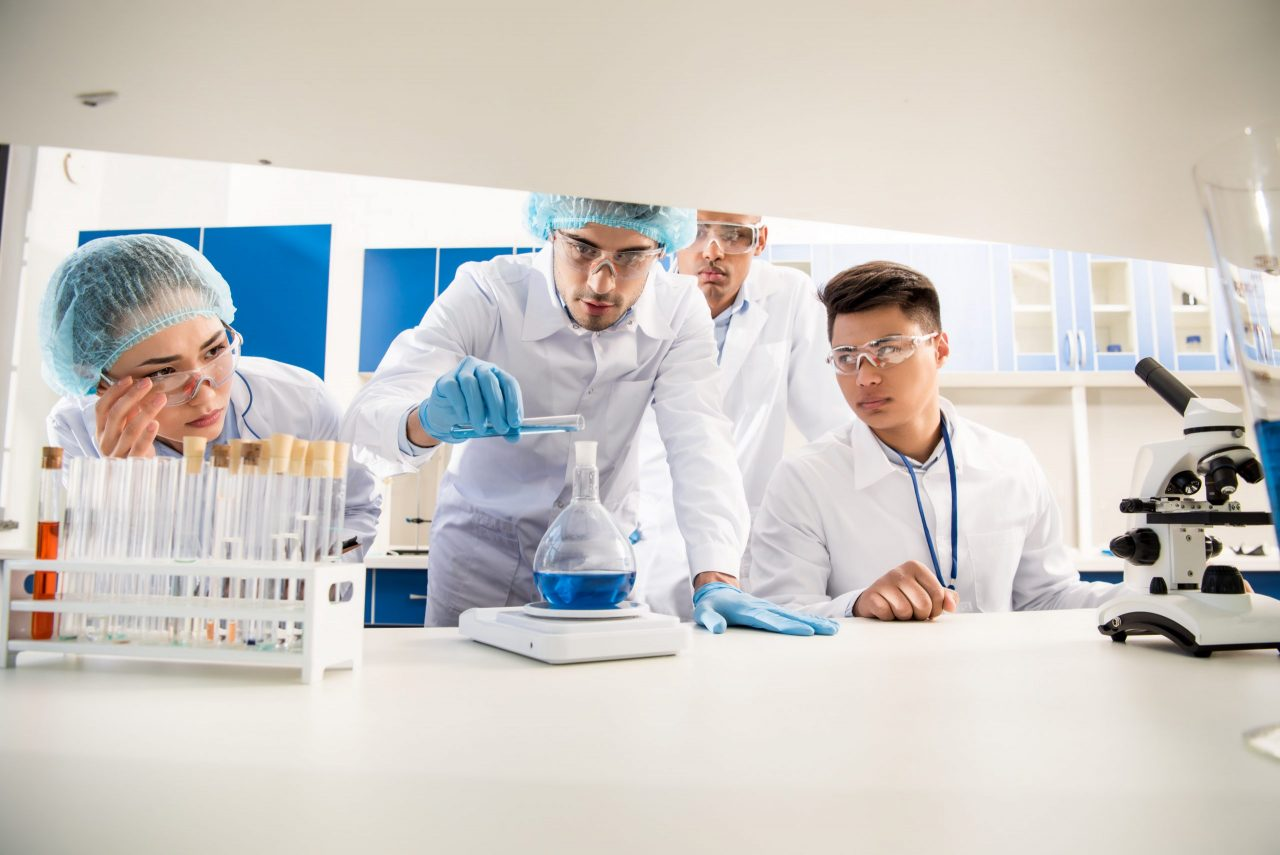group-of-medical-workers-weighing-a-flask-with-rea-V3R2YAG-scaled-1280x855.jpg